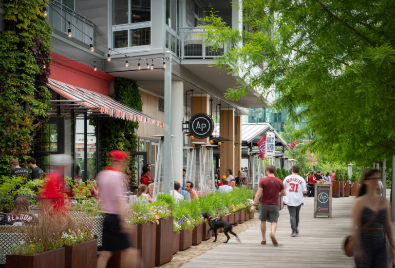 people walking along the waterfront near retail stores